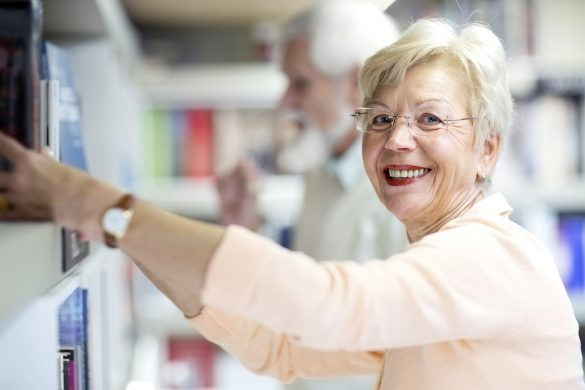 Older lady chooses book from library shelf
