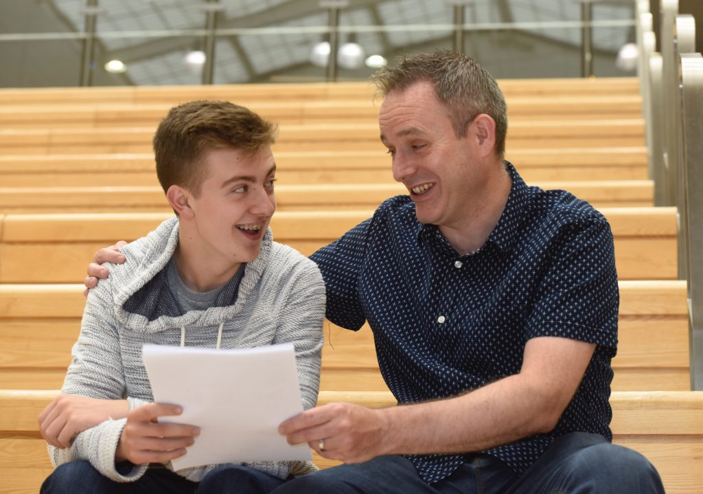 Gary Evans, Principal of Halewood Academy, congratulates student Alex Watson, who gained 9 GCSE passes including two A*