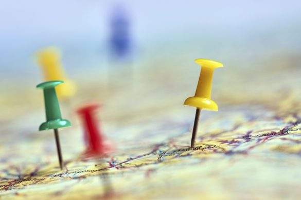 horizontal shot of colorful pins marking different traveling locations on map.