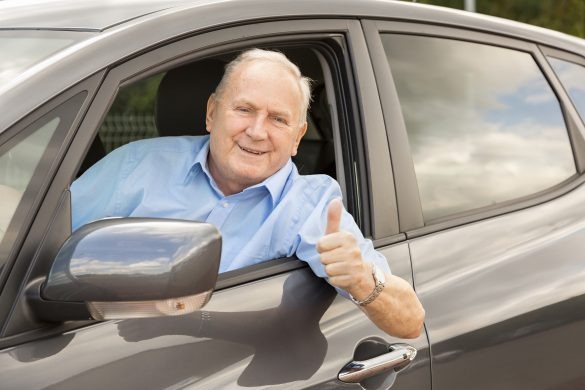 Senior man, over 70 years old, sitting in a car and showing a thumbs up