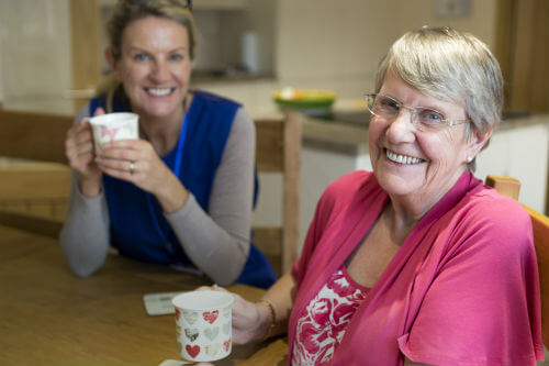 A female carer having a cup of tea with an elderly lady
