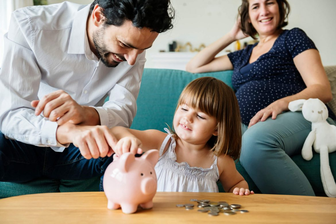 A mother and father with their child putting coins in the piggy bank