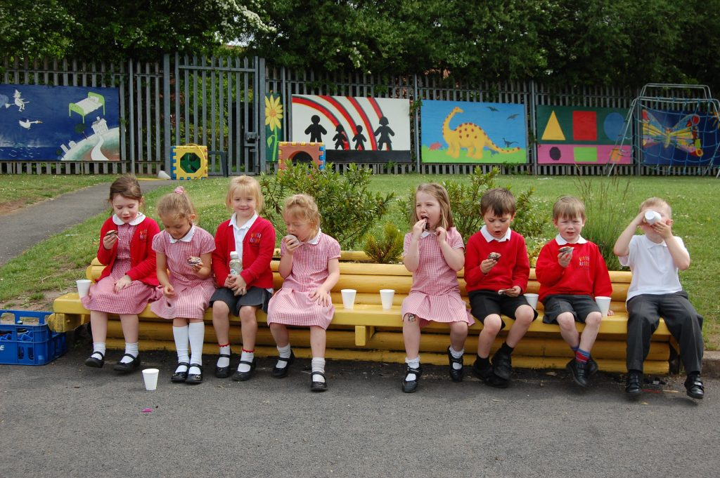 children with cakes on bench