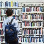 Man browses bookshelf at library