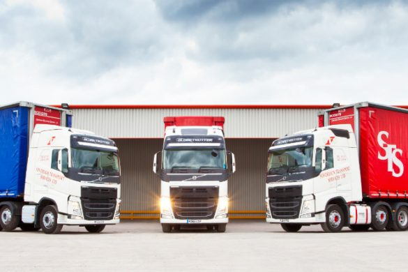 Three lorries pictured outside a transport depot with lights on