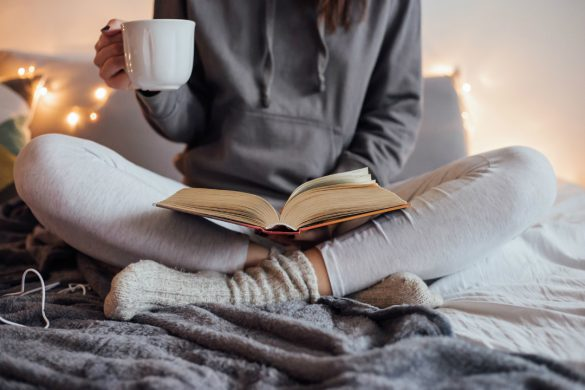 Woman reads book on her lap with cup of tea
