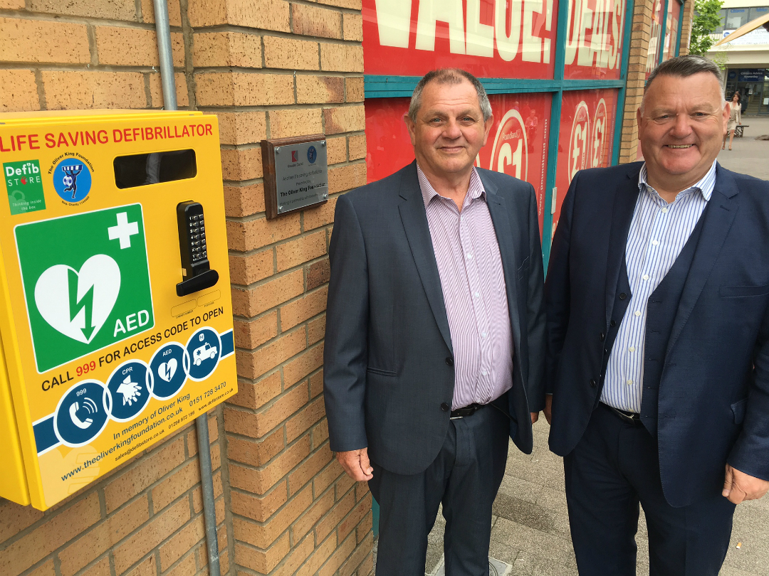 Cllr Byron and Mark King, from the Oliver King Foundation, with the defibrillator that has been installed in Kirkby Town Centre