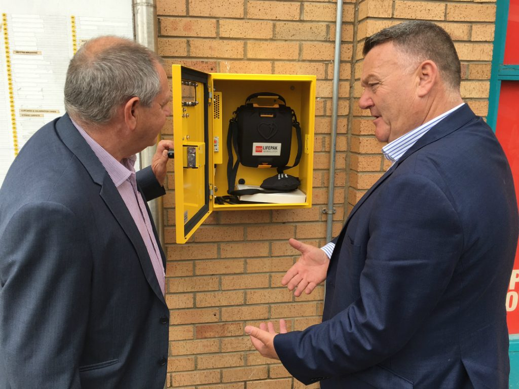 Mark King shows Cllr Byron inside the defibrillator box, which has been installed in Kirkby town centre