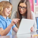 young child looks at tablet computer with adult female