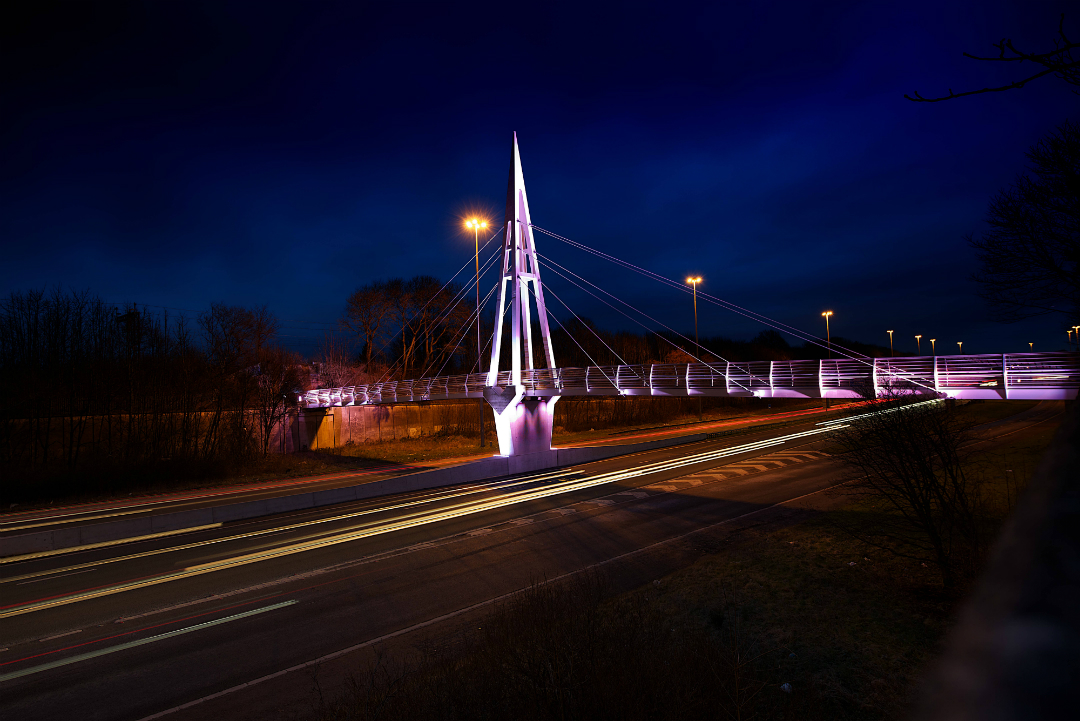 Greystone Footbridge over M62 in Huyton, Knowsley, illuminated in pink
