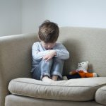 Sad toddler boy sitting on sofa