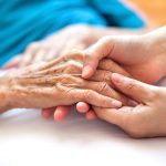 Elderly hands touching younger hands