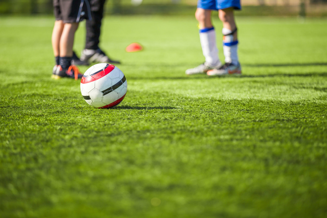 Grass pitch with youth football taking place